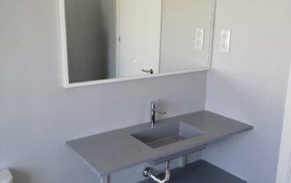 Encimera de baño con seno incorporado de 120x46 en color gris plomo colocada volada sobre soportes.